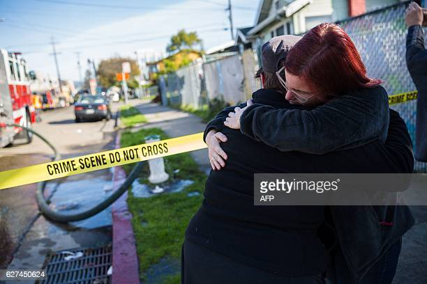 People gather near a warehouse after it was destroyed by a fire December 3 2016 in Oakland California Up to 40 people were feared dead in a huge fire...