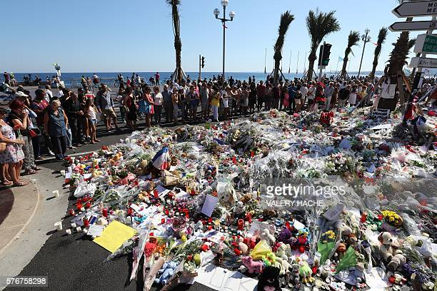 People gather near flowers placed at a makeshift memorial near the Promenade des Anglais in Nice on July 17 in tribute to the victims of the Bastille...