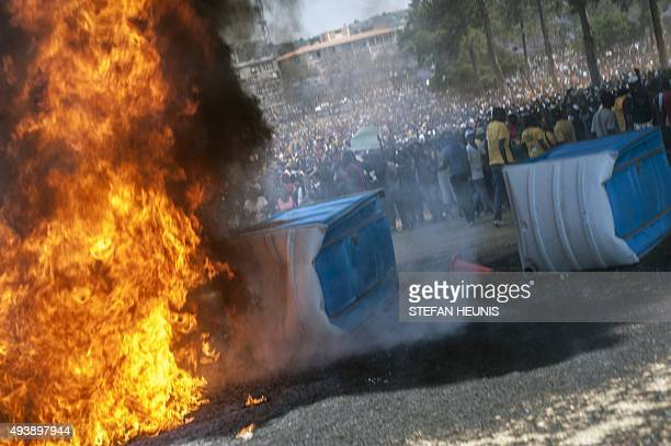 People gather near portable toilets set on fire during a student demonstration in front of the Union Buildings the seat of the government on October...