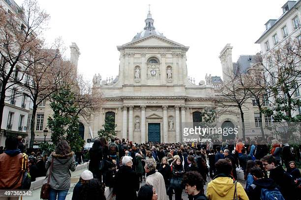 People gather near Sorbonne University to observe a minutesilence in memory of the victims of the Paris terror attacks last Friday in the 5th...