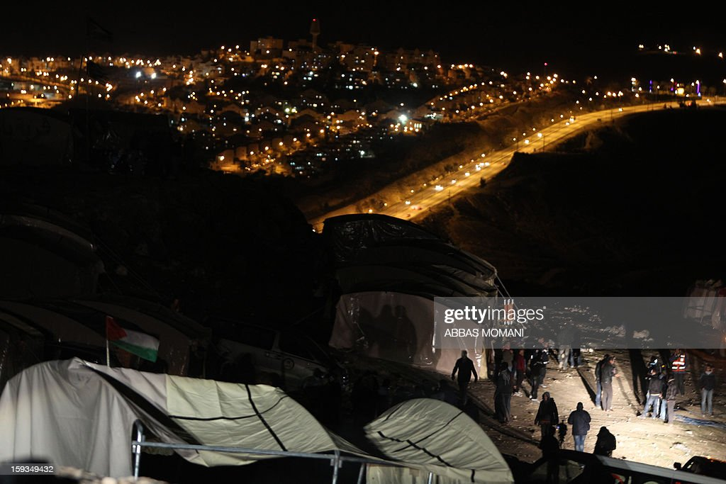 People gather near tents that Palestinian activists set up in an 'outpost' named Bab al-Shams ('Gate of the Sun') between Jerusalem and the Jewish settlement of Maale Adumim in the Israeli-occupied West Bank, in an area where Israel has vowed to build new settler homes, on January 12, 2013. After nightfall, the end of the Jewish sabbath, Prime Minister Benjamin Netanyahu's office said in a statement that he was seeking to have the injunction overturned. AFP PHOTO/ABBAS MOMANI