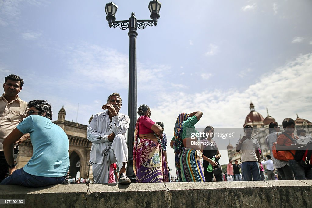 People gather near the Gateway of India memorial building in Mumbai, India, on Wednesday, Aug. 21, 2013. The prospect of an indecisive 2014 election in India is eroding confidence among global investors that the government can stop the rupees worst drop in more than two decades. Photographer: Dhiraj Singh/Bloomberg via Getty Images