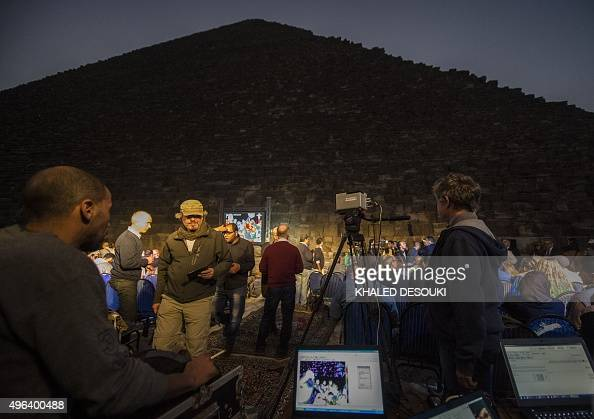People gather near the great pyramid of Khufu in Giza on the outskirts of Cairo on November 9 during an infrared thermography experiment to map out...