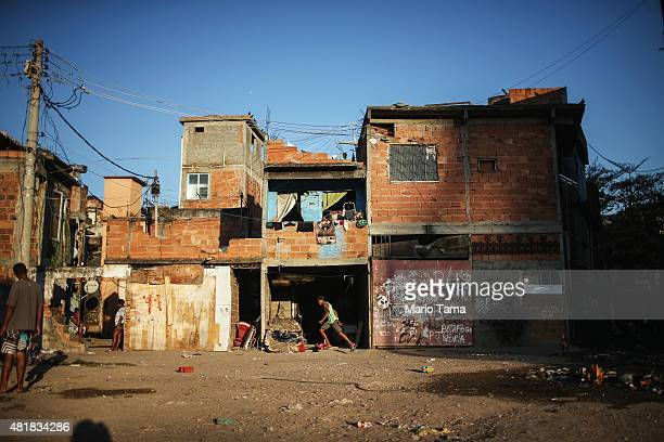 People gather near the rubble of destroyed homes in the MetroMangueira community or 'favela' located approximately 750 meters from Maracana stadium...