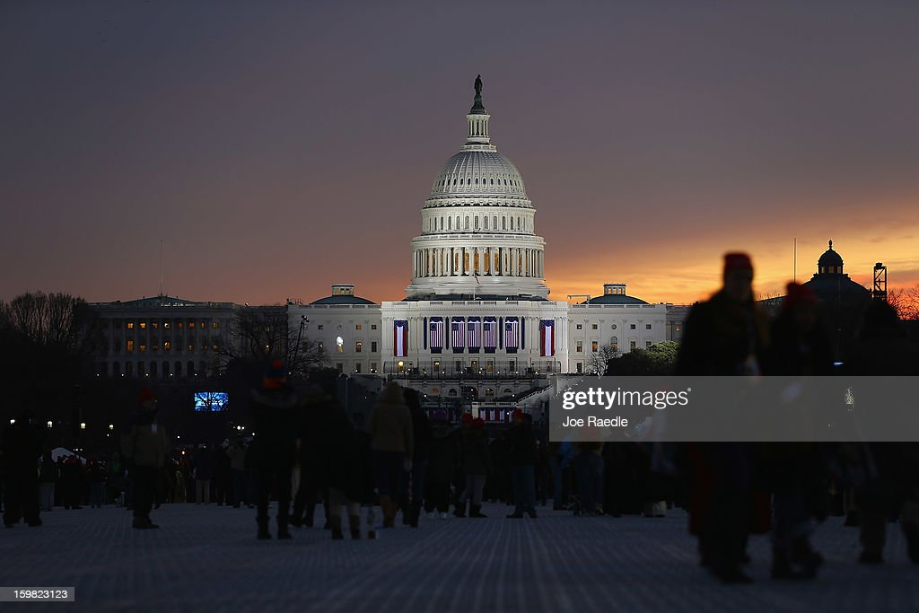People gather near the US Capitol building on the National Mall for the Inauguration ceremony on January 21 2013 in Washington DC US President Barack...