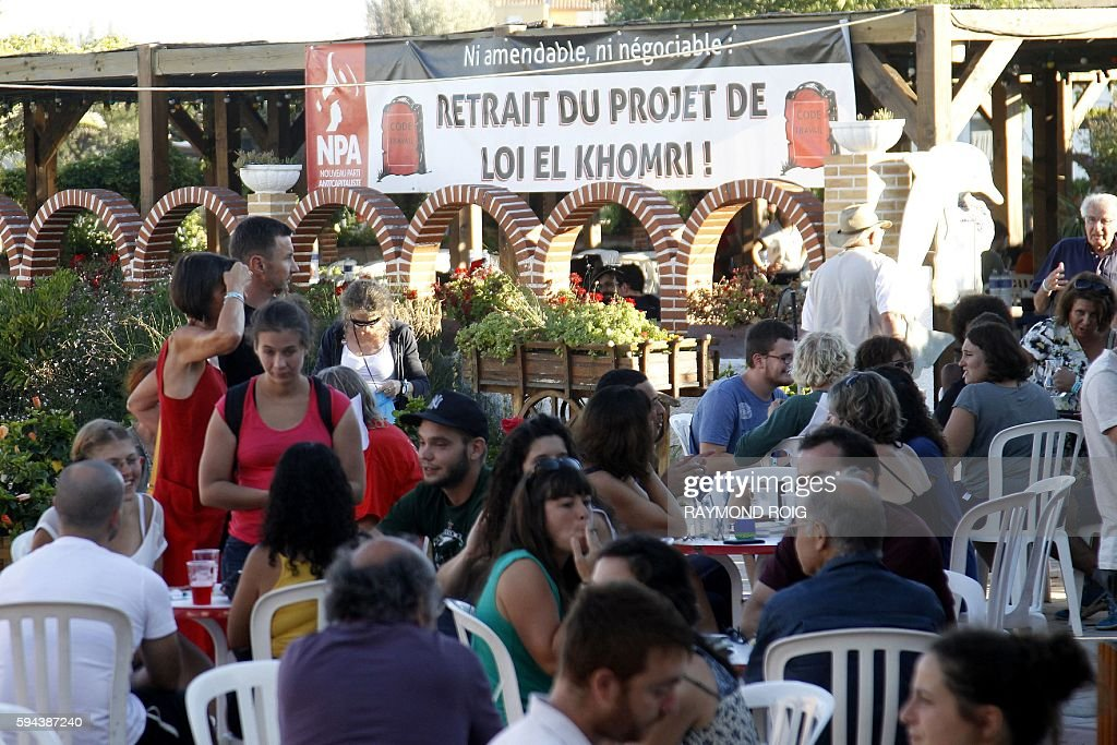 People gather next to a banner reading 'Removal of the El Khomri Labour law' during the summer gathering of the New AntiCapitalist Party in Leucate...