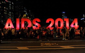 People gather next to a sign reading AIDS 2014 in Melbourne on July 18 2014 after news that downed Malaysia Airlines flight MH17 was carrying many...