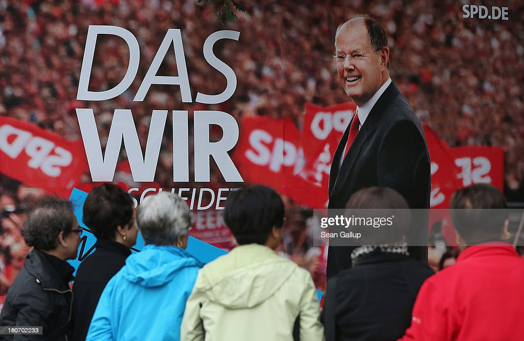 People gather next to an election campaign billboard of German Social Democrats (SPD) lead candidate Peer Steinbrueck on September 16, 2013 in Berlin, Germany. Germany faces federal elections on September 22 and so far the SPD has less than half the support in polls of the governing German Christian Democrats (CDU), though the election outcome could force the two parties to form a coalition.