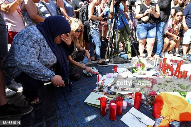People gather next to flowers candles and other items set up on the Las Ramblas boulevard in Barcelona as they pay tribute to the victims of the...
