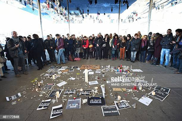 People gather next to signs reading ''I am Charlie'' and candles placed on the ground after observing a minute of silence in the old Harbor in...