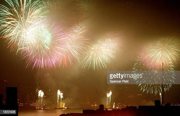 People gather on a Brooklyn rooftop to watch fireworks explode over New York City July 4 2001 as Americans celebrate Independence Day