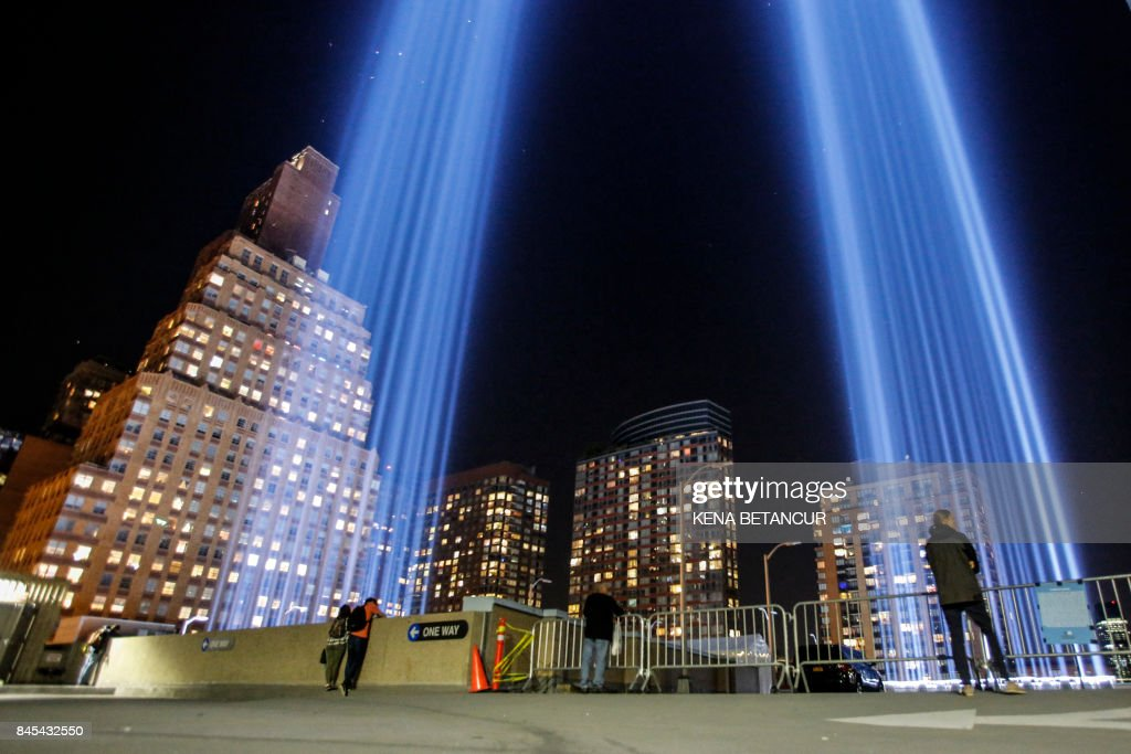 People gather on a rooftop as the 'Tribute in Light' illuminates the night sky, on September 10, 2017 in New York City, on the eve of the anniversary of the September 11, 2001 terror attacks. Commemorations are being held on the 16th anniversary of the 9/11 terror attacks, with President Donald Trump expected to speak at a ceremony for the 184 people killed at the Pentagon in Washington, DC. /