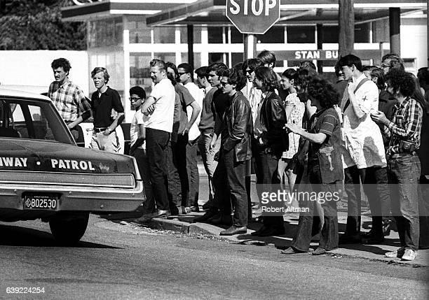 People gather on a street corner as a Highway Patrol car drives by near People's Park on May 16 1969 in Berkeley California