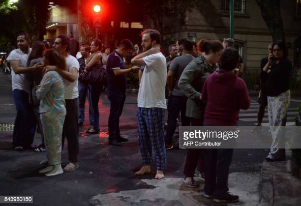 TOPSHOT People gather on a street in downtown Mexico City during an earthquake on September 7 2017 A powerful 80 magnitude earthquake struck southern...