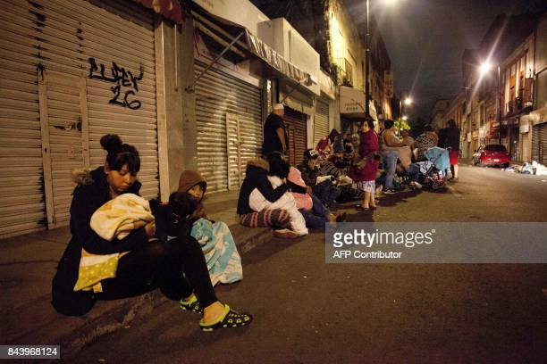 TOPSHOT People gather on a street in downtown Mexico City during an earthquake on September 7 2017 An earthquake of magnitude 80 struck southern...