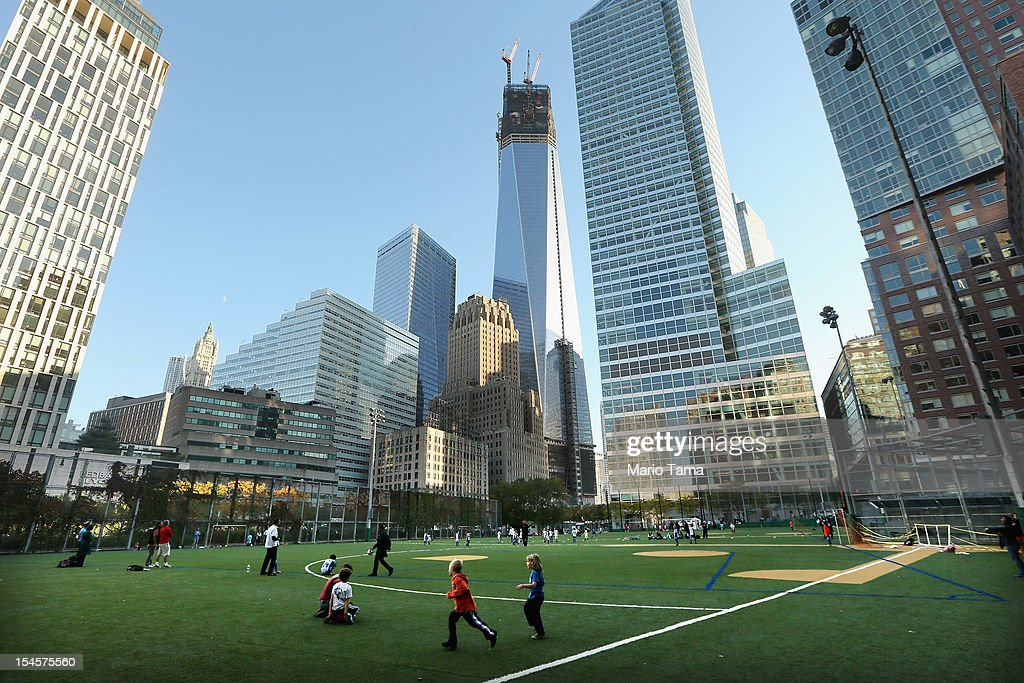 People gather on an athletic field in Lower Manhattan as One World Trade Center (TOP C) rises under construction on October 22, 2012 in New York City. The Census Bureau reported last month that between 2000 and 2010 the downtown population grew by nearly 40,000 people, in spite of the September 11 terrorist attacks at the World Trade Center. One World Trade Center is scheduled to open in 2014 at the symbolic height of 1,776 feet and will be the tallest building in the Western Hemisphere.