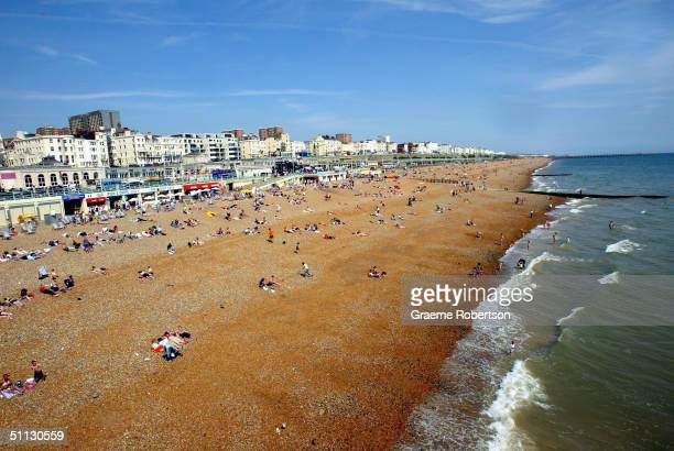 People gather on Brighton beach enjoying the sunshine on July 30 2004 in Brighton England The United Kingdom is set for soaring temperatures this...