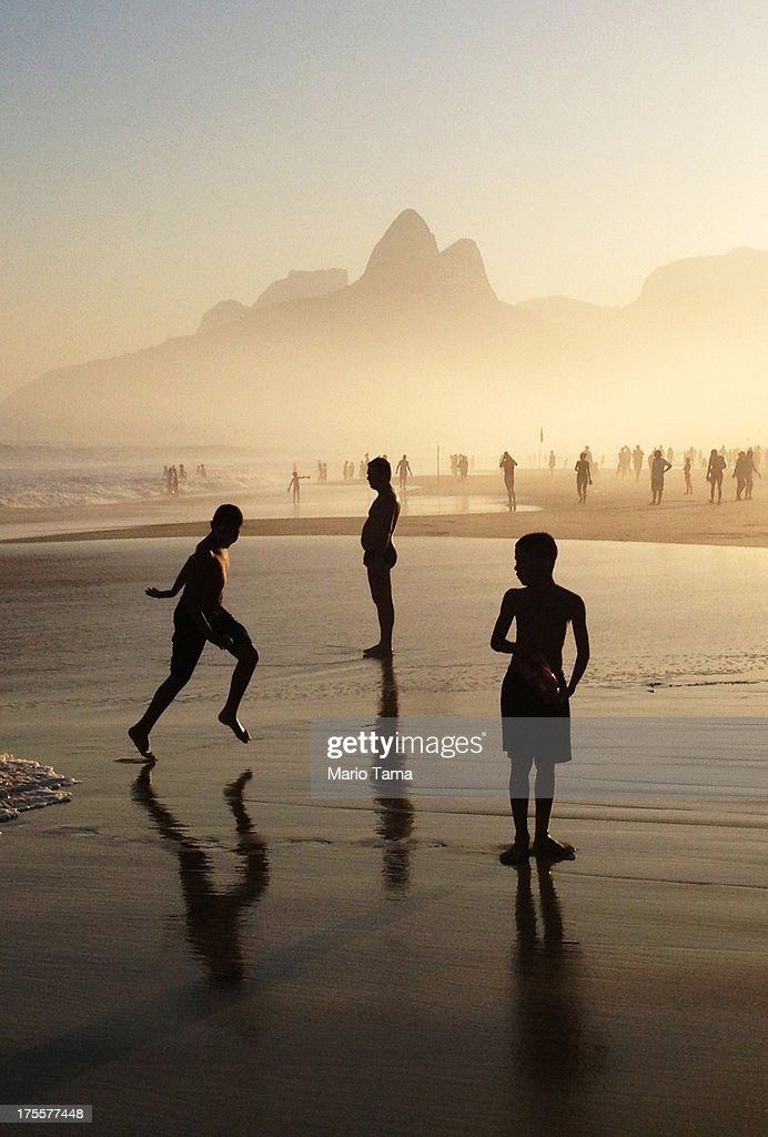 People gather on Ipanema Beach as the sun sets on August 4, 2013 in Rio de Janeiro, Brazil. Following Pope Francis' visit last week, Brazil's World Cup is set to begin in just over ten months.