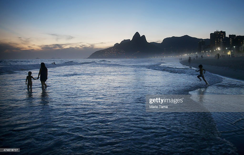 People gather on Ipanema Beach following a 'bloco' street party during pre-Carnival festivities on February 23, 2014 in Rio de Janeiro, Brazil. Carnival officially begins on February 28 but pre-festivities have already begun. Brazil is gearing up to host the 2014 FIFA World Cup.