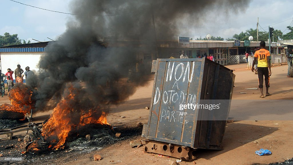 People gather on November 17, 2013 at the Sica-Benzvi square in Bangui as unrest erupt after the assassination of a magistrate the day before. The message on the container reads in French 'No to Dotodjia, leave' refering to President Michel Djotodia.