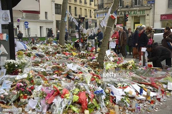 People gather on November 27 2015 in front of the cafe 'La Belle Equipe' on rue de Charonne in Paris' 11th district to mourn victims during a...