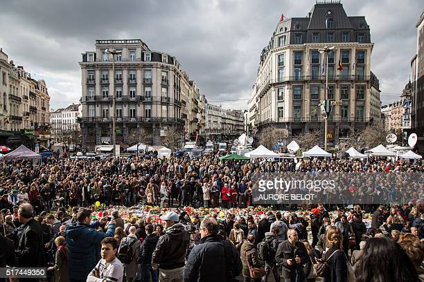 TOPSHOT People gather on Place de la Bourse square in Brussels to pay tribute to the victims of the Brussels terror attacks on March 25 2016 Grieving...