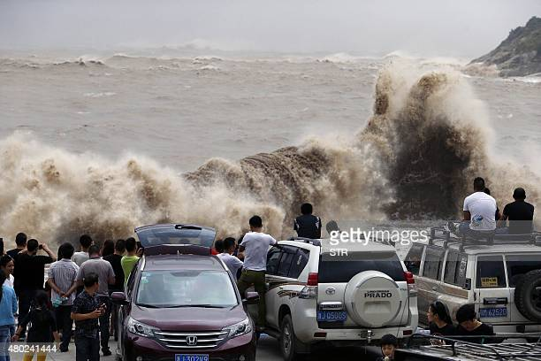 People gather on the bank to watch huge waves as typhoon Chanhom comes near Wenling east China's Zhejiang province on July 10 2015 Typhoon Chanhom...