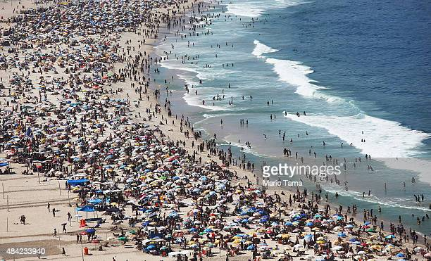 People gather on the beach during a protest calling for the impeachment of President Dilma Rousseff along Copacabana beach on August 16 2015 in Rio...