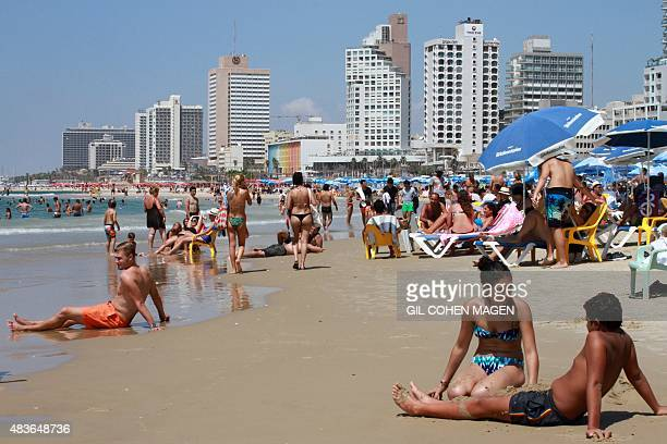 People gather on the beach in the Israeli Mediterranean city of Tel Aviv on August 11 2015 Decision to dedicate a day of beach parties in the French...