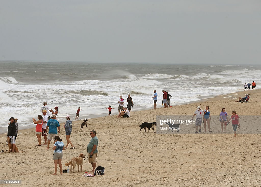 People gather on the beach near heavy surf left by Hurricane Arthur, July 4, 2014 in Avalon, North Carolina. Hurricane Arthur hit North Carolina's outer banks overnight causing widespread power outages, flooding and damage, and has since weakened to a Category 1 as of Friday morning.