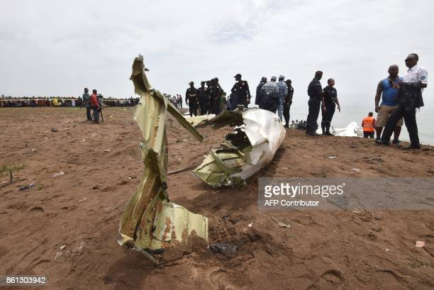 People gather on the beach of PortBouet in Abidjan on October 14 2017 to look at the the wreckage of a cargo plane that crashed off Ivory Coast...