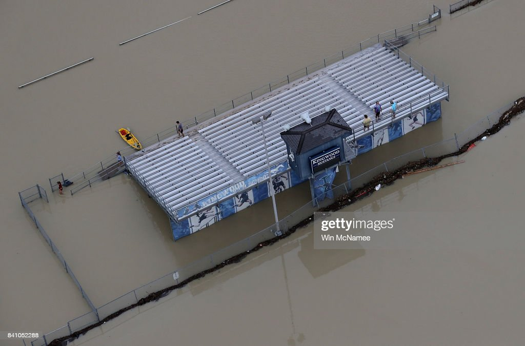 People gather on the bleachers of a flooded high school football field near Lake Houston following Hurricane Harvey August 30, 2017 in Houston, Texas. The city of Houston is still experiencing severe flooding in some areas due to the accumulation of historic levels of rainfall, though the storm has moved to the north and east.