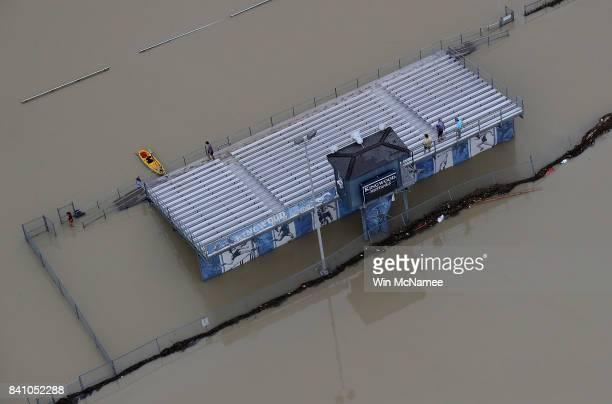 People gather on the bleachers of a flooded high school football field near Lake Houston following Hurricane Harvey August 30 2017 in Houston Texas...