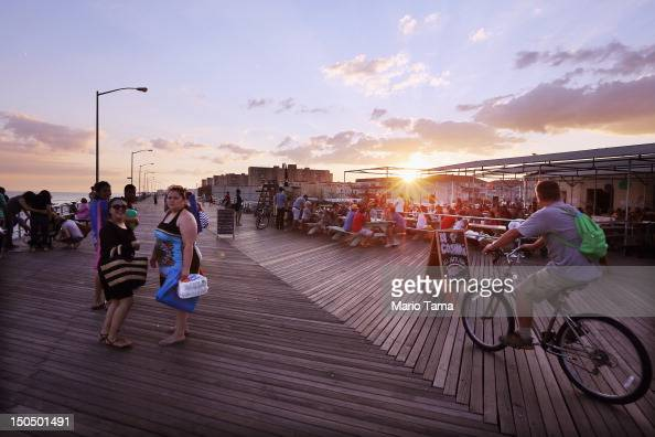 People gather on the boardwalk at Rockaway Beach on August 18 2012 in the Queens borough of New York City Over the last few years the Rockaways...
