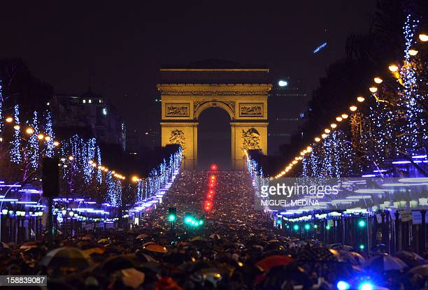 People gather on the ChampsElysees avenue in Paris to celebrate the New Year late on December 31 2012 AFP PHOTO / MIGUEL MEDINA