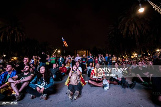 People gather on the floor of the square to follow the speech of the Catalan President Carles Puigdemont in the regional Parliament in downtown...