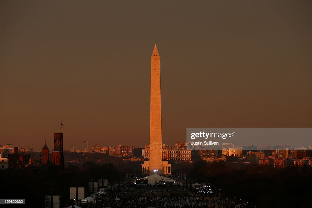 People gather on the mall in the early morning in front of the Washington Monument before the presidential inauguration on the West Front of the U.S. Capitol January 21, 2013 in Washington, DC. Barack Obama was re-elected for a second term as President of the United States.