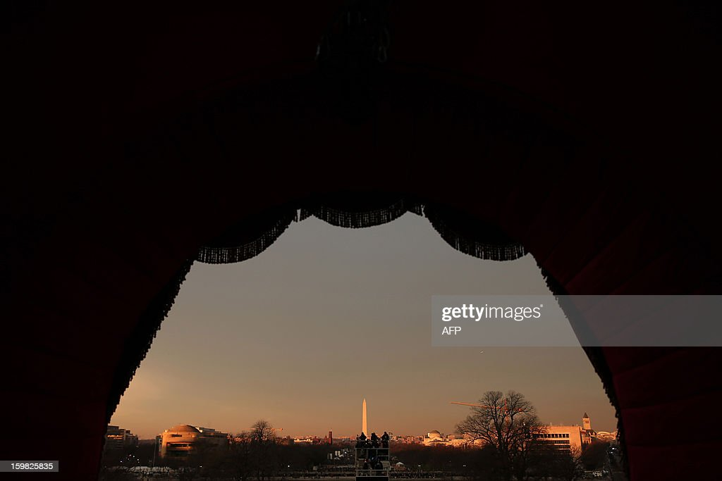 People gather on the mall in the early morning in front of the Washington Monument before the presidential inauguration on the West Front of the US Capitol on January 21, 2013 in Washington, DC. Barack Obama was re-elected for a second term as President of the United States.
