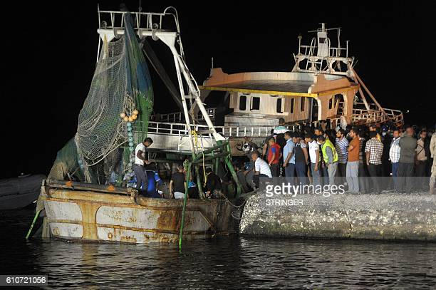 People gather on the quay as a wreck of a migrant boat raised by the Egyptian navy and maritime rescuers arrives in the Egyptian port city of Rosetta...