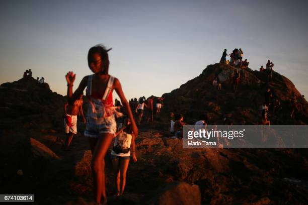 People gather on the rocks by the Barra lighthouse on April 19 2015 in Salvador Brazil