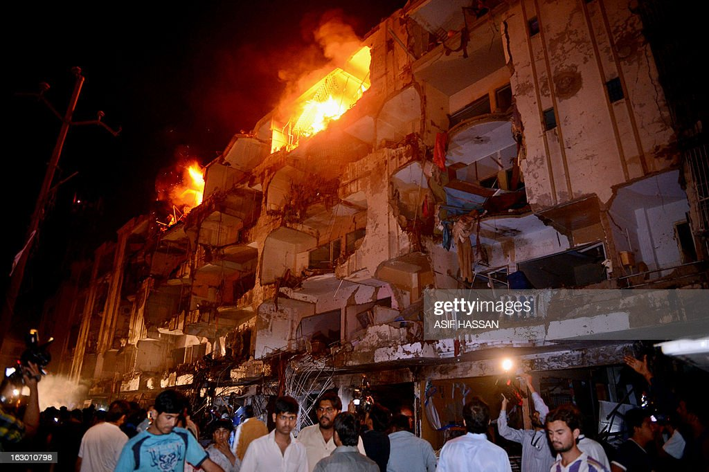 People gather on the site of bomb blast in Karachi on March 3, 2013. A bomb attack in Pakistan's largest city Karachi on Sunday killed at least 23 people, including women and children, and wounded 50 others, police said. AFP PHOTO/ASIF HASSAN