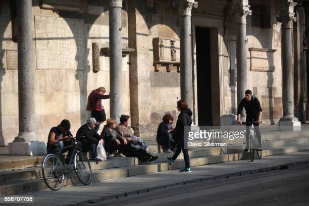 People gather on the steps of the Cattedrale di Santa Maria Assunta the city's Duomo or Cathedral on March 25 2017 in Cremona Italy The city is noted...