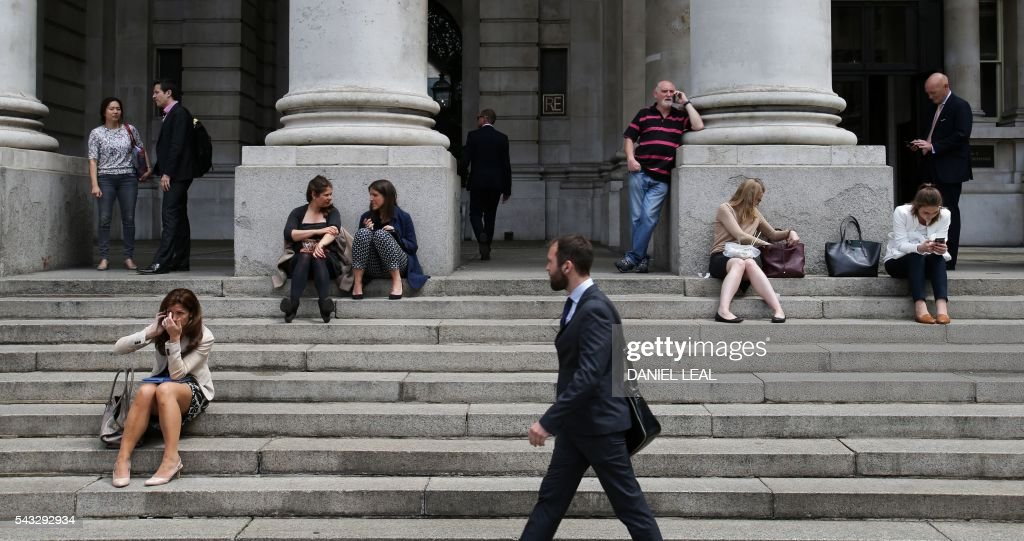 People gather on the steps of the Royal Exchange, near the Bank of England in the City of London on June 27, 2016. Britain should only trigger Article 50 to leave the EU when it has a 'clear view' of how its future in the bloc looks, finance minister George Osborne said Monday following last week's shock referendum. London stocks extended their losses in early afternoon Monday, led by banking, airline and property shares, following Britain's vote to leave the EU. / AFP / Daniel Leal-Olivas