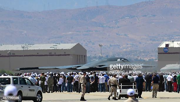 People gather on the tarmac for a closer look as a B2 Stealth Bomber passes on way to take off at the Palmdale Aircraft Integration Center of...