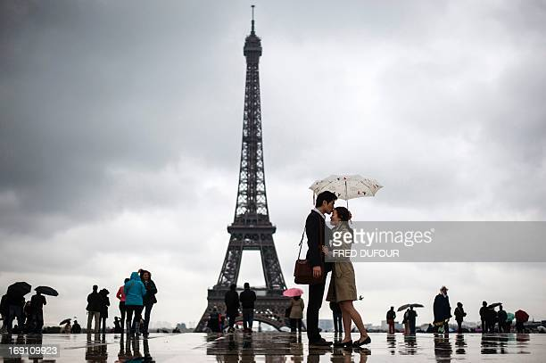 People gather on the Trocadero Square in front of the Eiffel Tower on a rainy day on May 20 in Paris AFP PHOTO / FRED DUFOUR / AFP PHOTO / Fred DUFOUR