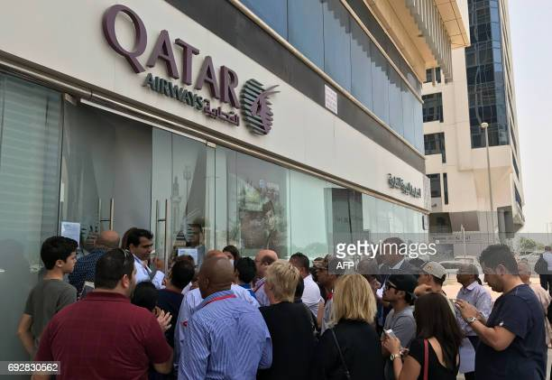 People gather outside a branch of Qatar Airways in the United Arab Emirate of Abu Dhabi on June 6 2017 A ban on Qatari flights imposed by Saudi...