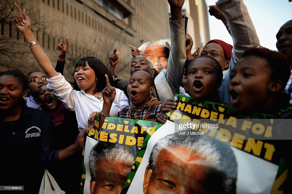 People gather outside ANC headquarters to pray and sing for Nelson Mandela on July 2, 2013 in Johannesburg, South Africa. Nelson Mandela's ex-wife Winnie Madikizela-Mandela recently said that the Nobel peace prize laureate's condition has shown 'great improvement' but he is still critically ill.