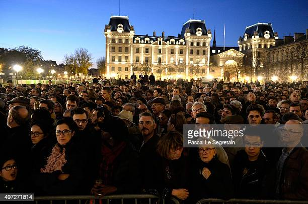 People gather outside Notre Dame Cathedral ahead of a ceremony to the victims of the friday's terrorist attacks on November 15 2015 in Paris France...