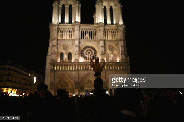People gather outside Notre Dame cathedral during a ceremony to honour the victims of friday's terrorist attacks on November 15 2015 in Paris France...