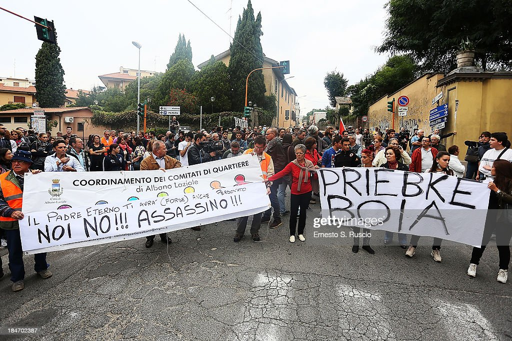 People gather outside the church of Lefebvriani to protest with a banner which says 'Priebke Executioner' on October 15, 2013 in Albano Laziale, Italy. The funeral of Erich Priebke, a former SS officer convicted of participating in the massacre of 335 citizens in Italy during World War II will now take place at the Lefebvriani Chapel in Albano Laziale, after the Catholic Church announced in a statement soon after his death that 'no public funeral would be granted to him in the city or outskirts of Rome'. His burial is not yet settled after his German hometown refused to allow his burial there.